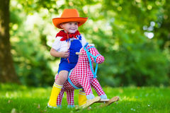 Child playing with a toy horse. Little boy dressed up as cowboy playing with his toy rocking horse in a summer park. Kids play outdoors. Children in Halloween Royalty Free Stock Images