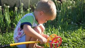 A child is playing with a toy on the lawn. Entertainment and outdoor games stock video