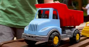 Child playing with toy truck. Crop hand of child with sand holding toy truck and driving it on bench stock video footage