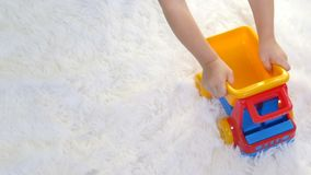 A child playing with a toy truck, in slow motion, on a white background. Slow motion stock footage