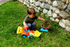 Child playing with toy trucks Royalty Free Stock Image
