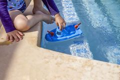 Young Boy By The Side Of Swimming Pool. Isolated. Child playing with toy tugboat. Stock Image royalty free stock photo