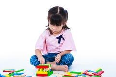 Child playing toy wood blocks, isolated on white background. Royalty Free Stock Images