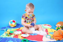 Child playing toys. A child playing toys on a blue background Royalty Free Stock Photography