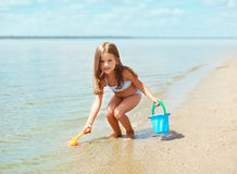 Child playing with toys and having fun on the beach near sea Royalty Free Stock Image