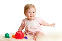 Child is playing with toys while sitting on floor Stock Photography