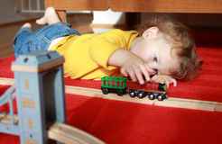 Child Playing with Trains at Home. Child, toddler boy, playing at home with trains and tracks royalty free stock photos