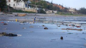 Child playing among plastic garbage and trash on sand on seashore. Pan shot. Child playing among the trash and rubbish on sand of seashore.Pan shot stock video