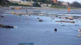 Child playing among plastic garbage and trash on sand on seashore. Pan shot. Child playing among the trash and rubbish on sand of seashore.Pan shot stock video footage