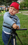 Child playing with tripod Royalty Free Stock Photography