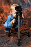 Child playing with tripod Royalty Free Stock Images