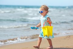 Child playing on tropical beach. Little girl digging sand at sea shore. Kids play with sand toys. Travel with young children stock photo