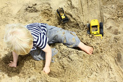 Child Playing Trucks in Sandbox Stock Image