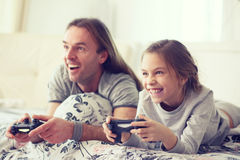 Child playing video game with father. Child playing video game on tv with father in morning at bed at home Royalty Free Stock Photo