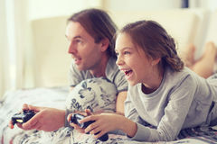 Child playing video game with father. Child playing video game on tv with father in morning at bed at home Stock Images