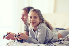 Child playing video game with father. Child playing video game on tv with father in morning at bed at home Royalty Free Stock Photography