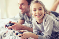 Child playing video game with father. Child playing video game on tv with father in morning at bed at home Stock Photos