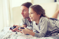 Child playing video game with father. Child playing video game on tv with father in morning at bed at home Royalty Free Stock Photos