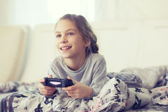 Child playing video game. On tv in morning at parent's bedroom at home Royalty Free Stock Photo