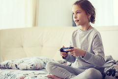 Child playing video game. On tv in morning at parent's bedroom at home Royalty Free Stock Photography