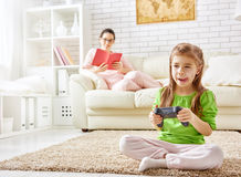Child playing video games. Family relax. mother reading a book, child playing video games Royalty Free Stock Photography
