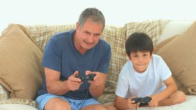 A child playing video games with his grandfather stock footage