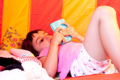 Child playing video games. Little girl playing video games inside her playhouse Stock Photo