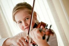 Child playing violin. Cute child (little girl) playing violin and exercising at home Stock Image