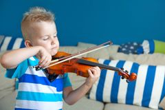 The child is playing the violin. Boy studying music. stock photos