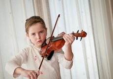 Child playing violin at home Stock Images