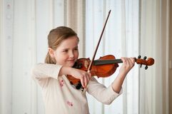 Child playing violin indoors. Cute child (little girl) playing violin and exercising at home Royalty Free Stock Photos