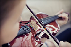 Child playing a violin. Young girl practicing playing music on a violin Royalty Free Stock Images