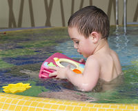 Child playing in water  in children pool Stock Photos
