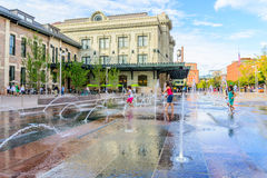 Child playing in a water feature in front of Union Station in Denver Colorado Stock Photos