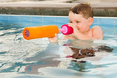 Child playing with water gun while swimming Royalty Free Stock Images