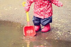Child playing in water puddle, kids outdoor Royalty Free Stock Photo