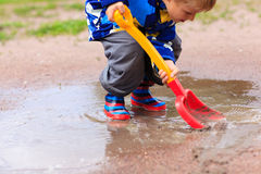 Child playing in water puddle, kids spring activities Stock Photo