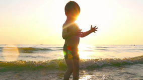Child is playing with water on a sea beach, in the incoming waves, against the background of sunset. A child is playing with water on a sea beach, in the stock footage