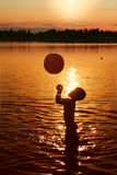 Child playing in water at sunset. Child playing in the lake at beautiful summer sunset royalty free stock images