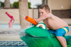 Child playing with water toy at kiddie pool Royalty Free Stock Photos