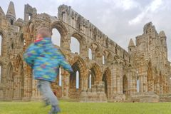 Whitby abbey ruin, yorkshire, uk. A child playing in Whitby Abbey ruin in Yorkshire, famous for providing inspiration for Bram Stoker`s Dracula on an overcast Stock Photo