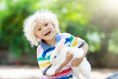 Child with rabbit. Easter bunny. Kids and pets. Child playing with white rabbit. Little boy feeding and petting white bunny. Easter celebration. Egg hunt with stock photography