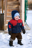 Child playing in winter snow. Young boy wearing warm winter clothing stood in winter snow smiling Royalty Free Stock Photo