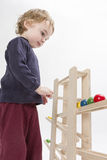 Child playing with wooden ball path Stock Photography