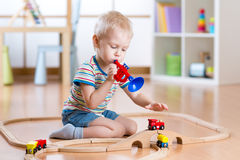 Child playing with wooden railway on the floor in nursery. Little boy plays a pipe imagining the train driver that gives Stock Photos