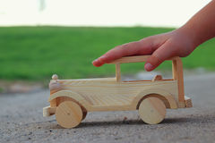 Child playing with wooden toy car on the road outdoors in the park royalty free stock images