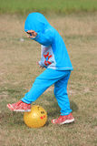 Child is playing with a yellow ball. Child is playing in the field Stock Photo