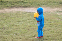 Child is playing with a yellow ball. Child is playing in the field Royalty Free Stock Images