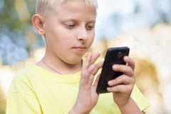 Child playing on your smartphone Royalty Free Stock Image