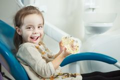 Child plays with artificial human jaw in dentist chair. Child plays with artificial human jaw with involved face expression in comfortable leather dentist chair stock photo